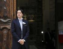 Bräutigam wartet auf die Braut an der Kirchentür Stockfotos