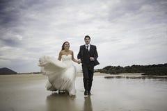 Bräutigame, die Strand laufen lassen Lizenzfreie Stockfotografie