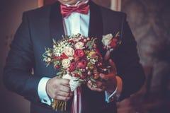 Bräutigamwartebraut mit einem Blumenstrauß stockfotografie