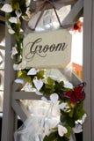 Bräutigamzeichen auf Hochzeitsbogen mit Blumen Stockfoto