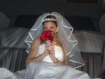 Bräutliche blonde Frau auf Limousine mit Blumenstrauß Stockfotos