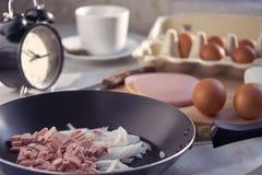 Brådskande förberedelse av en frukost av stekte ägg i morgonen, innan att lämna för arbete arkivfoton