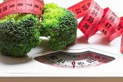 Brócolis com a fita de medição na escala do peso dieting fotos de stock