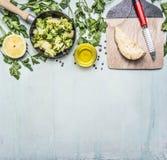 Brócolis crus em uma bandeja com ervas, limão, raiz de aipo em uma placa de corte com uma beira da faca, texto do lugar no backg  Imagem de Stock Royalty Free