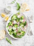 Brócolis da mola e salada do rabanete com molho em um fundo claro, vista superior do iogurte Alimento saudável delicioso do veget Foto de Stock Royalty Free