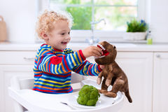 Brócolis de alimentação do rapaz pequeno ao dinossauro do brinquedo Fotografia de Stock Royalty Free