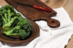 Brócolis em uma placa da argila, em uma placa de corte e na faca Fotos de Stock Royalty Free