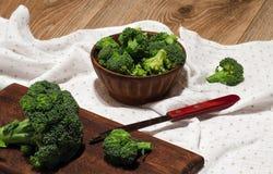 Brócolis em uma placa da argila, em uma placa de corte e na faca Imagem de Stock