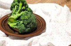 Brócolis em uma placa da argila na tabela Foto de Stock