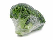 Brócolis envolvidos na folha plástica isolada no fundo branco fotos de stock