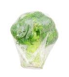 Brócolis no isolado da película de plástico (trajeto de grampeamento) imagens de stock royalty free