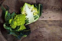Brócolis romanos de Romanesco do caulifloweror, inteiro e meio em um rus Foto de Stock