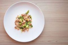 Brócolis salteado com carne de porco no prato branco Fotos de Stock