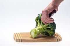 Brócolis vegetais com a mão que guarda uma faca no backround branco Imagem de Stock