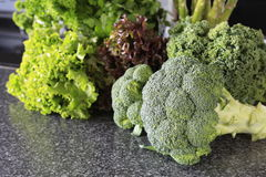 Brócolis verdes frescos com alface em uma tabela Fotos de Stock