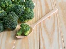 Brócolis verdes frescos com a colher no fundo de madeira Imagens de Stock