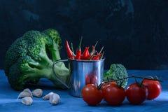 Bróculi, ajo y tomates rojos Aún vida hermosa en un oscuro Pimienta de chile en un pequeño cubo luz inusual Imágenes de archivo libres de regalías