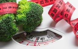 Bróculi con la cinta métrica en escala del peso dieting fotografía de archivo