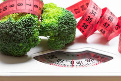 Bróculi con la cinta métrica en escala del peso dieting fotos de archivo