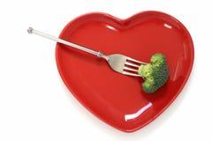 Bróculi en una fork y una placa roja de la dimensión de una variable del corazón Imagenes de archivo