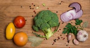 Bróculi fresco, corte en mitades con los tomates ajo y especias Foto de archivo