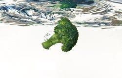 Bróculi que cae en el agua Fotos de archivo