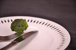 Bróculi verde fresco en la placa blanca sobre fondo de madera Imagen de archivo libre de regalías