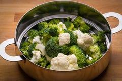 Bróculi y coliflor frescos en colador del acero inoxidable Fotos de archivo