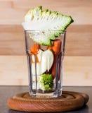 Bróculi, zanahorias y manzanas en un vidrio vacío Imágenes de archivo libres de regalías