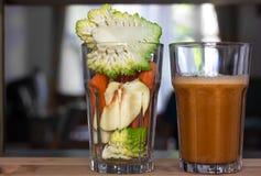 Bróculi, zanahorias y manzanas en un vidrio vacío y un vidrio lleno con el smoothie fresco Imágenes de archivo libres de regalías