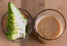 Bróculi, zanahorias y manzanas en un vidrio vacío y un vidrio lleno con el smoothie fresco Fotos de archivo libres de regalías