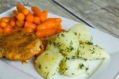 Bröad kotlett med kokta potatisar och moroten Fotografering för Bildbyråer