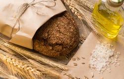 Bröd, öron, korn och grönsakolja på säckväv Arkivfoton