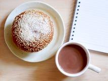 Bröd, en kopp av kakao och anteckningsbok Royaltyfria Bilder