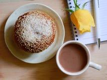 Bröd, en kopp av kakao och anteckningsbok Arkivfoto