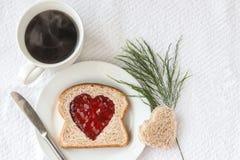 Bröd för helt vete med hjärtaform som ut klipptes, fyllde med rött driftstopp och koppen kaffe Arkivbilder