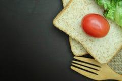 Bröd för helt vete med tomater och sallad på svart bakgrund Royaltyfri Bild