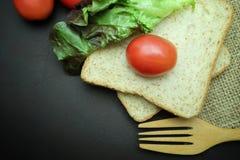 Bröd för helt vete med tomater och sallad på svart bakgrund Royaltyfri Fotografi