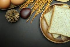 Bröd för helt vete på trämaträtt på svart bakgrund Royaltyfria Bilder