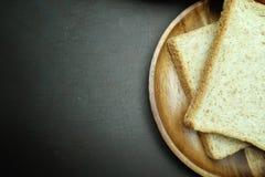 Bröd för helt vete på trämaträtt på svart bakgrund Arkivfoton