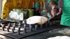 Bröd för lägenhet för manmatlagningindier som kallas chapatiroti naan paratha och grilla den på den levande flamman lager videofilmer
