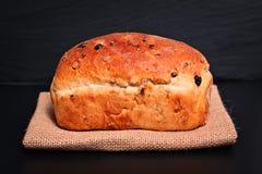Bröd för russin för vete för matbakgrund organiskt franskt helt på den svarta bakgrundsplattan Royaltyfri Bild