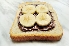 Bröd med chokladpralin och skivor av bananen Arkivfoto