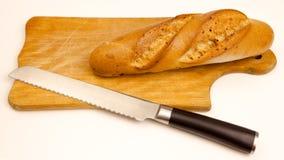 Bröd med en kniv på en skärbräda, på vit bakgrund Arkivfoton