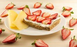 Bröd med jordgubben, ost, jordgubbe på tabellen royaltyfria bilder