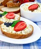 Bröd med ostmassa och bär på den blåa torkduken Royaltyfria Foton