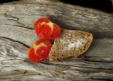 Bröd med salt och två skivor av tomat Arkivbild