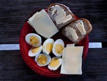 Bröd med smör, ost och kokta ägg på den röda plattan royaltyfria bilder