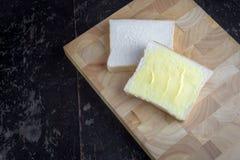 Bröd med smör på skärbräda Arkivbild