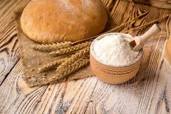 Bröd med vetemjöl, grova spikar och korn på trätabellen Agric Royaltyfria Bilder
